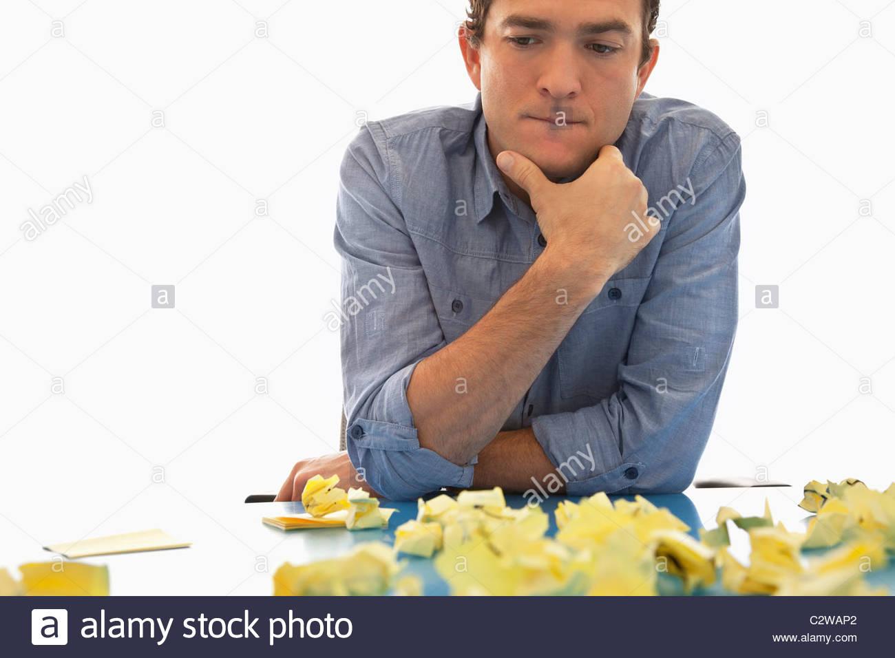 Businessman looking at crumpled adhesive notes - Stock Image