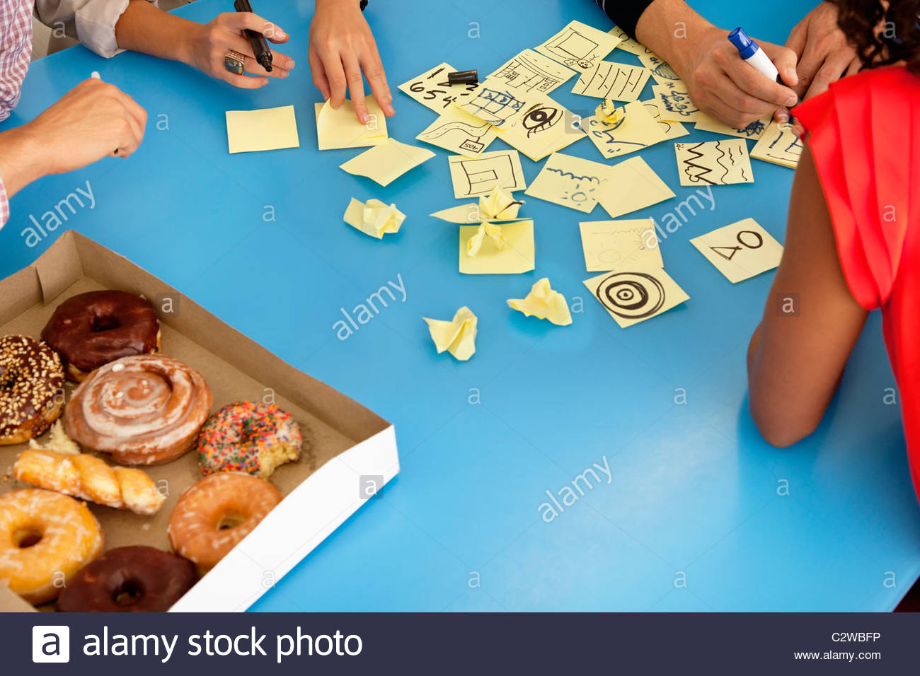 Business people with donuts writing on adhesive notes - Stock Image