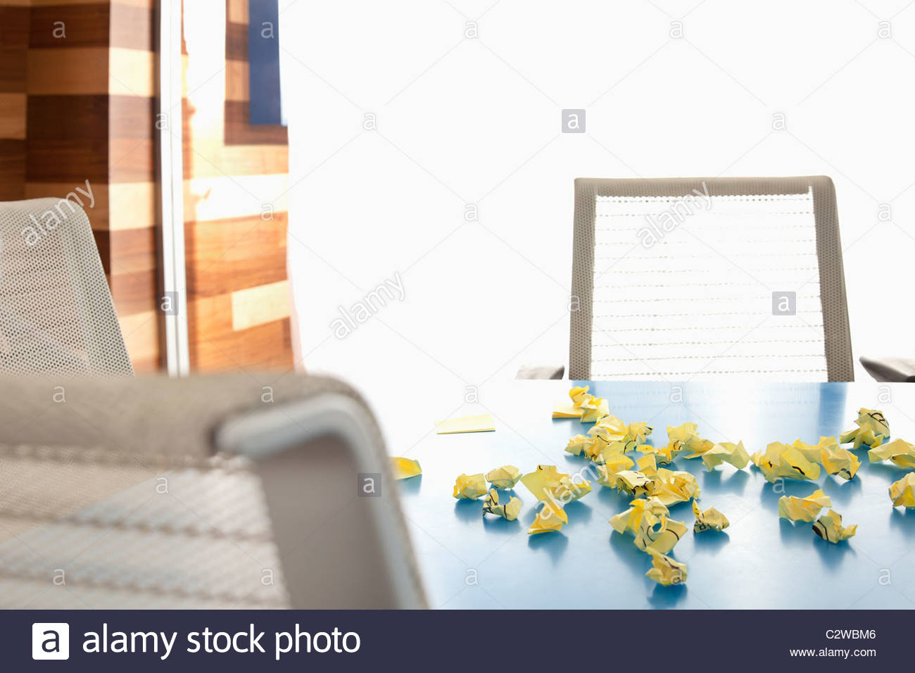 Crumpled adhesive notes on conference room table - Stock Image