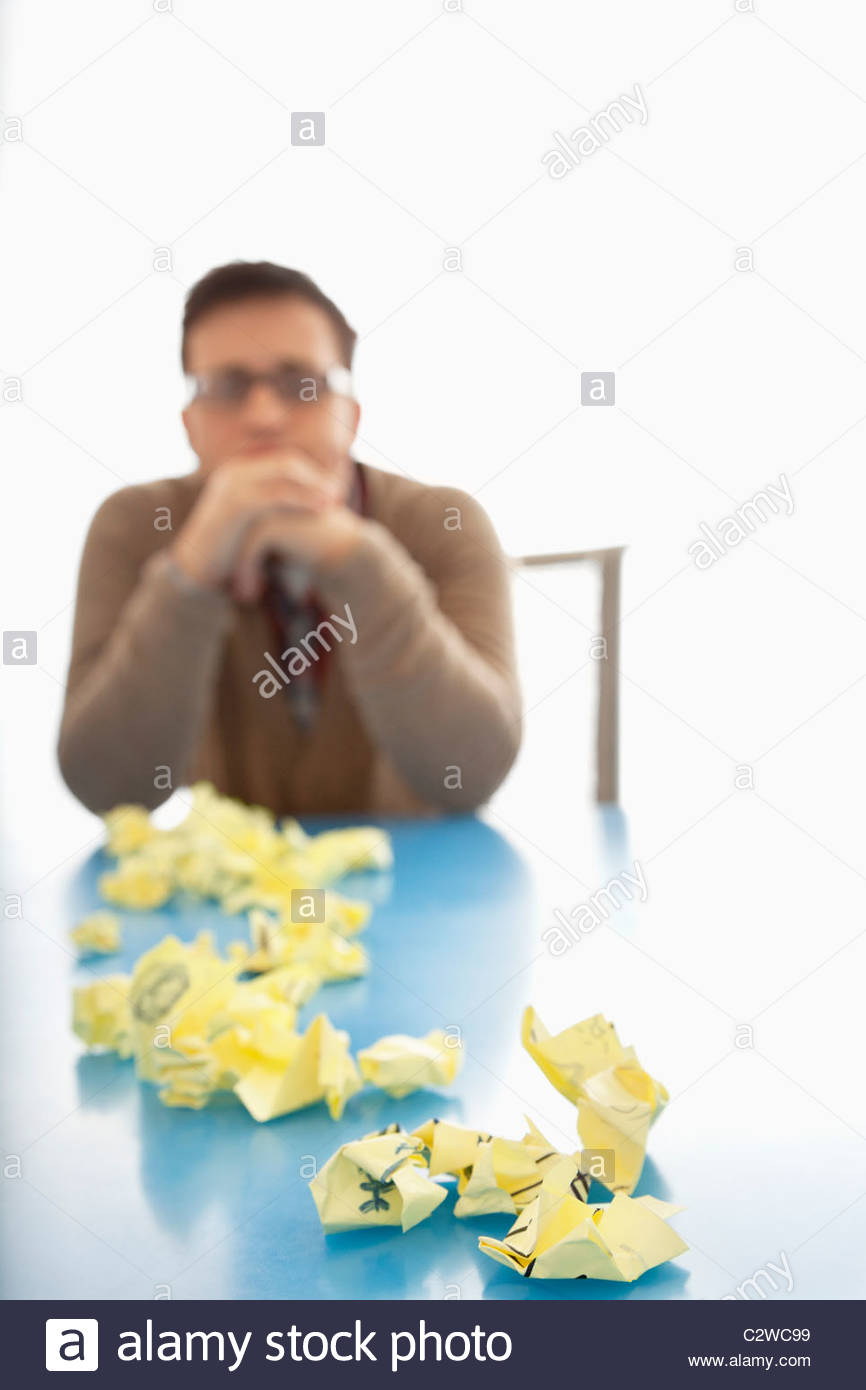 Businessman sitting at table with crumpled adhesive notes - Stock Image