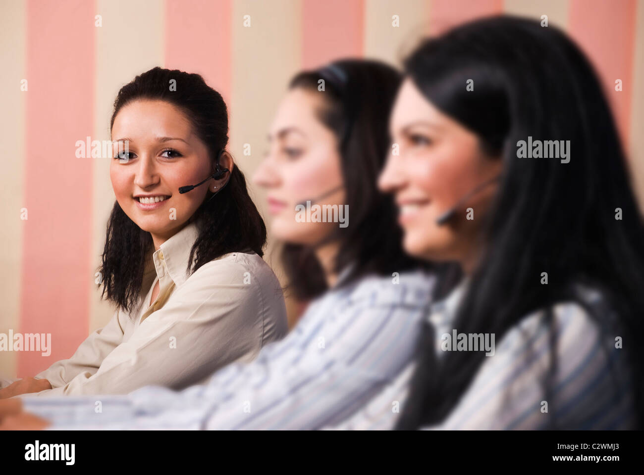 Three women customer service team sitting in line at desktop ,focus on last young woman which looked at you and Stock Photo