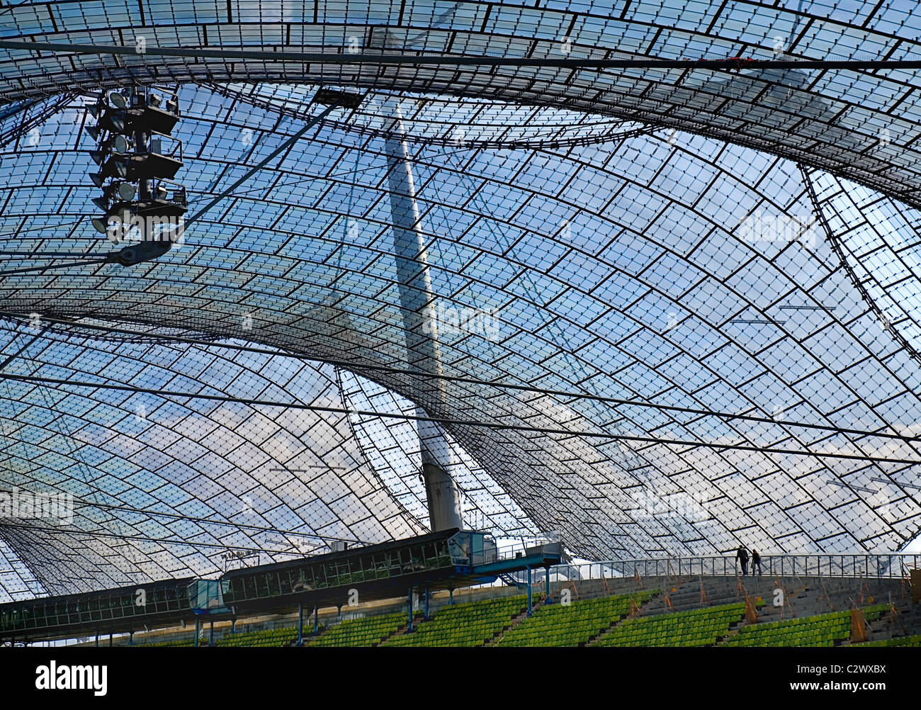 Germany Bavaria Munich 1972 Olympic Stadium curved section of bright green seating under canopy roof of acrylic - Stock Image