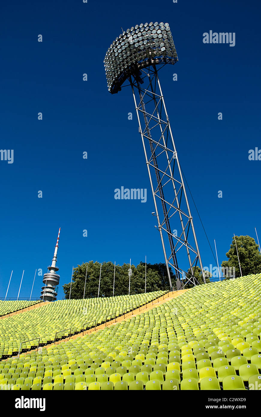 Germany Bavaria Munich Olympic Stadium curved section of bright green seating floodlights and Olympic Tower. - Stock Image