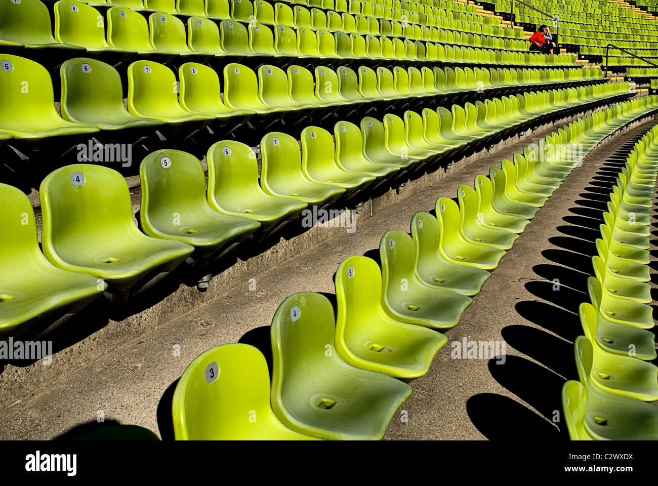 Germany Bavaria Munich Olympic Stadium curved section of bright green seating with single person seated. Stock Photo