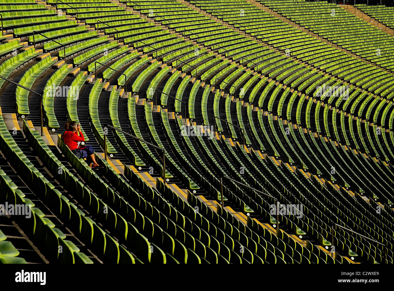 Germany Bavaria Munich Olympic Stadium curved section of bright green seating with single person seated. - Stock Image