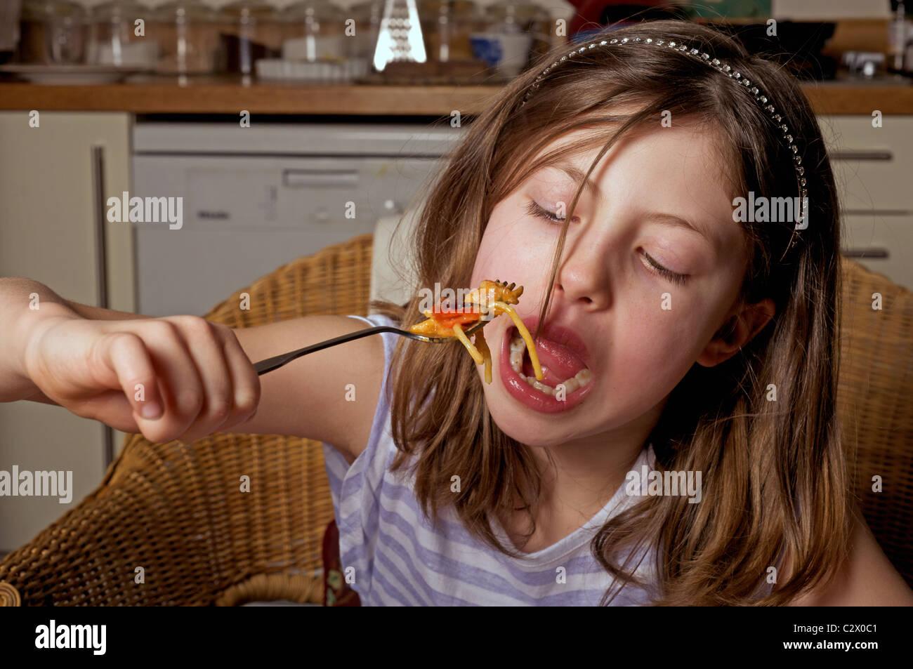 Young British girl eating spaghetti - Stock Image