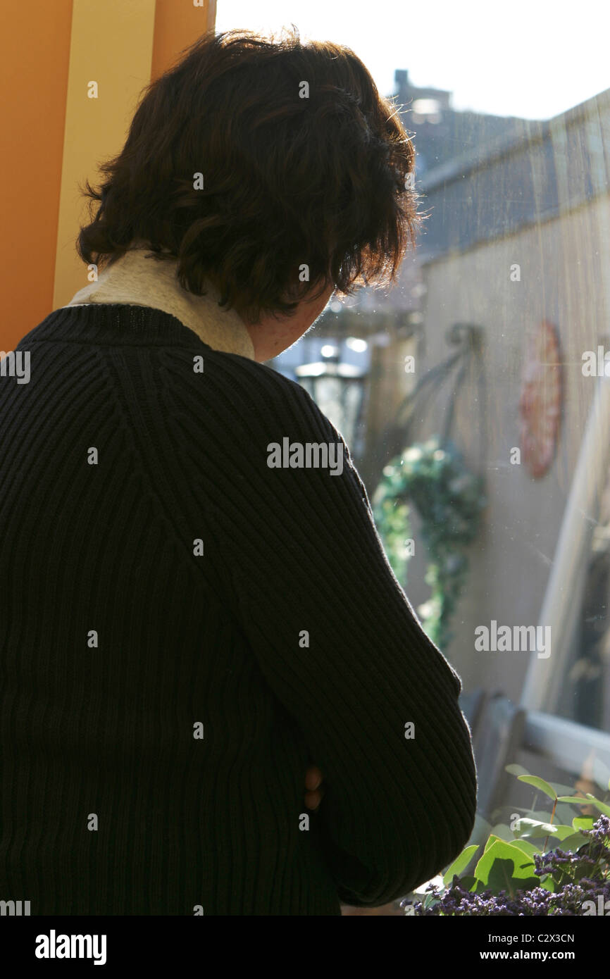 Back view lonely mature woman alone sadness, looking out of window at home. Stock Photo