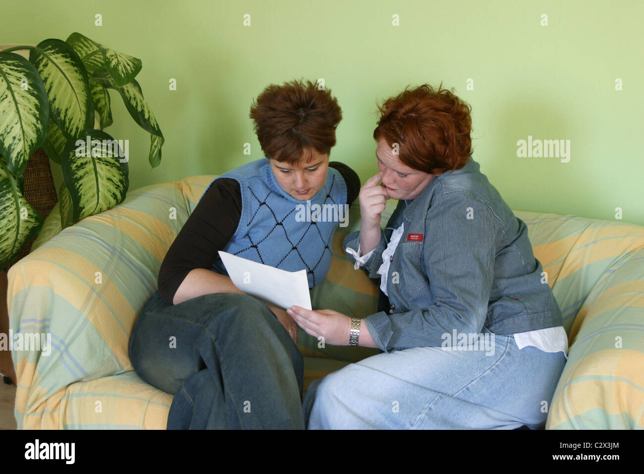Women on sofa reading contract or written letter on sofa. Th ladies are looking together at the paper holding in - Stock Image
