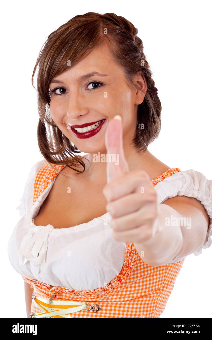 Junge, hübsche, bayerische Frau im Dirndl zeigt Daumen nach oben. Isoliert auf weißem Hintergrund. Stock Photo
