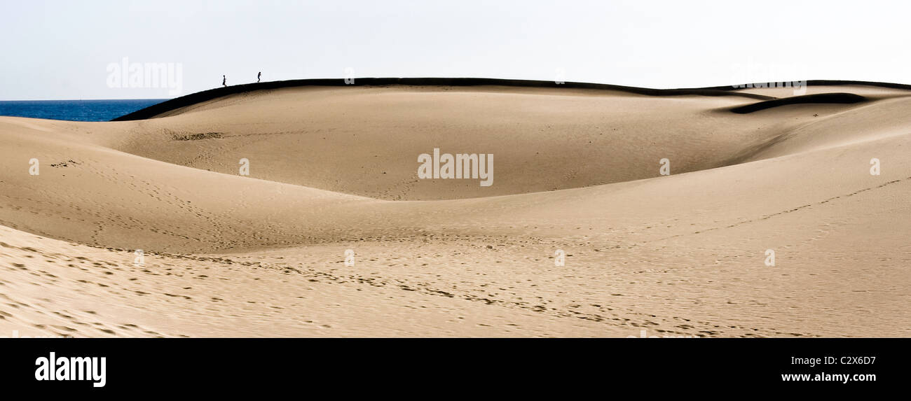 Gentle dunes in Gran Canaria, with attractive shapes and shadows. Two lonely people enjoy their walk on top of one - Stock Image