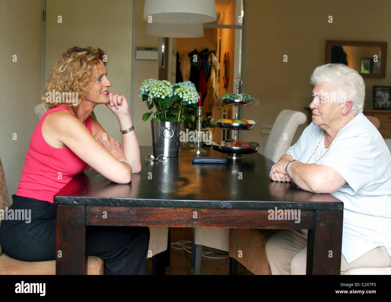 Old mother and grown up daughter having a conversation at the dining table - Stock Image