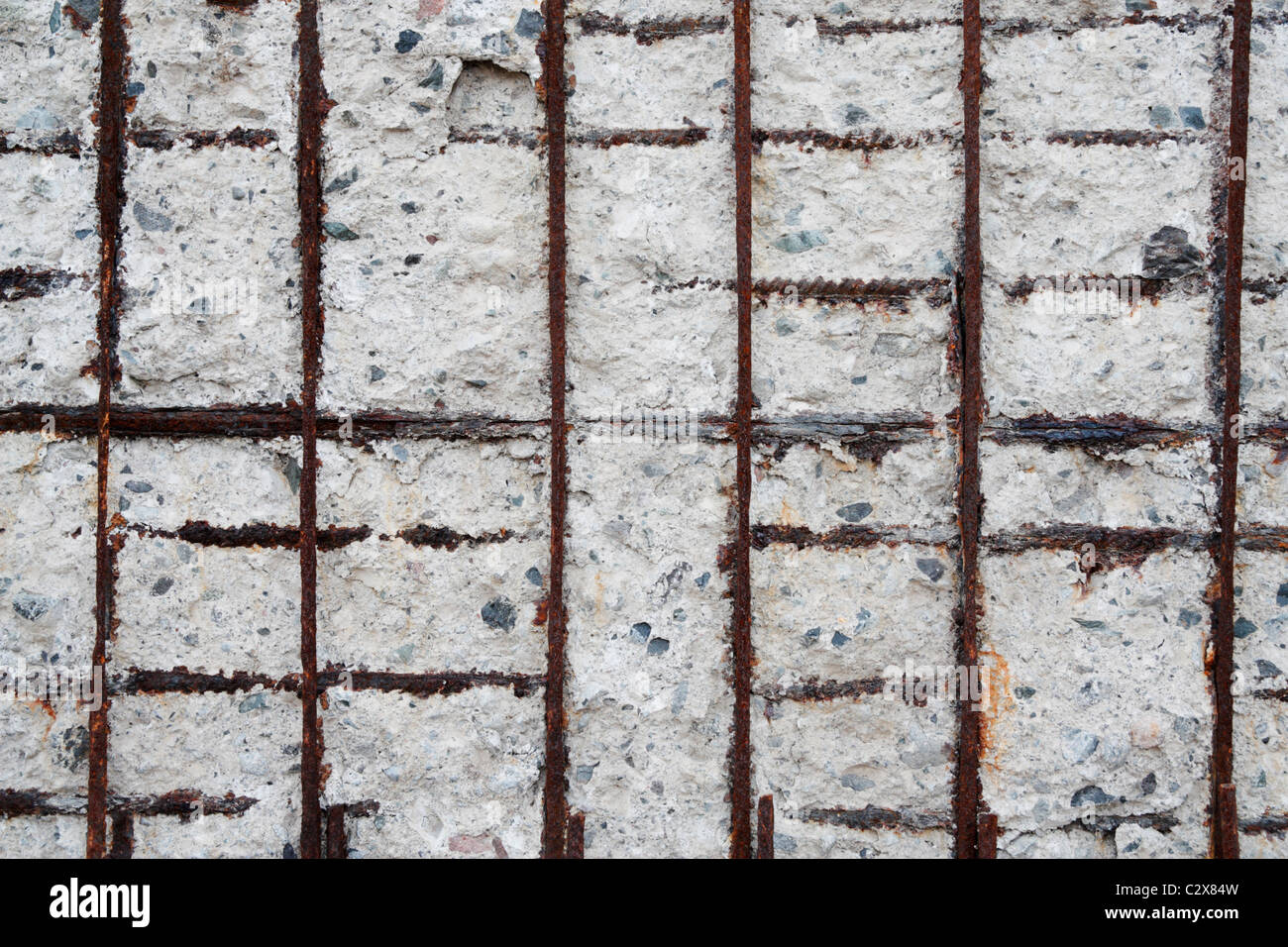 Reinforced concrete sea wall showing salt and weather damage - Stock Image