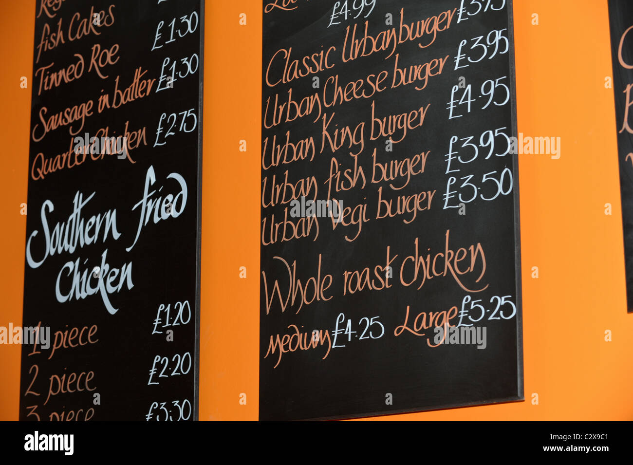Fast food menu on a blackboard  listing southern fried chicken, sausage in batter, classic burgers and whole roast - Stock Image