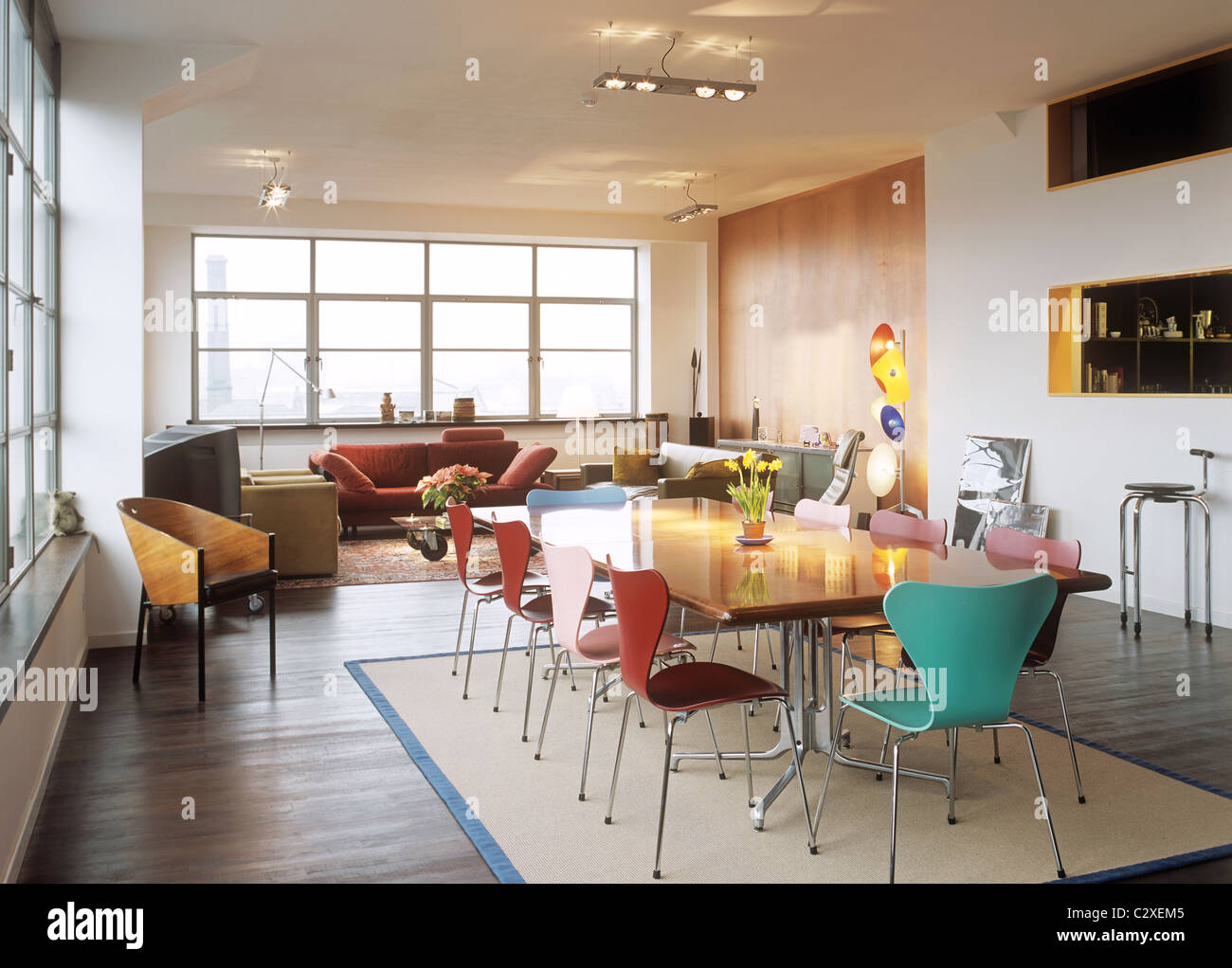 Wood Dining Table With Colored Arne Jacobsen Chairs Stock Photo