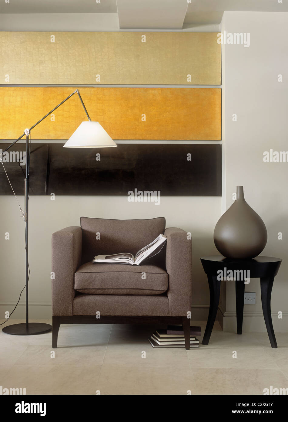 Contemporary artwork above upholstered armchair next to floor lamp - Stock Image