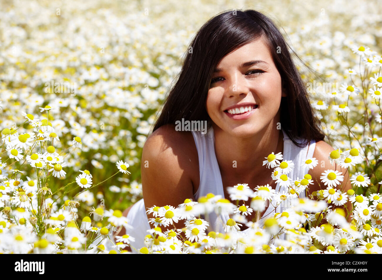 Image of happy female peeking out of chamomile glade and smiling - Stock Image