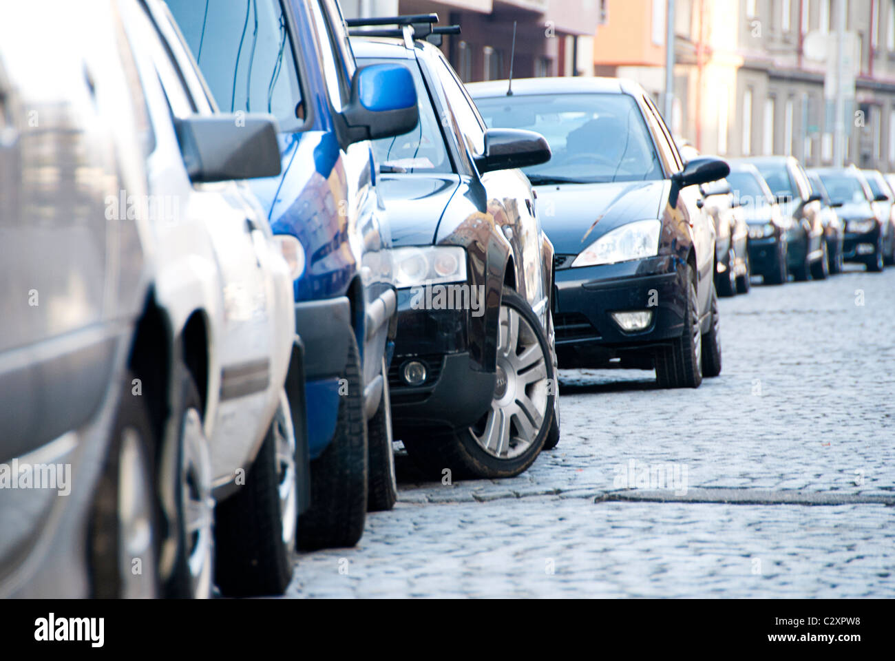 row of cars parked on city street - Stock Image