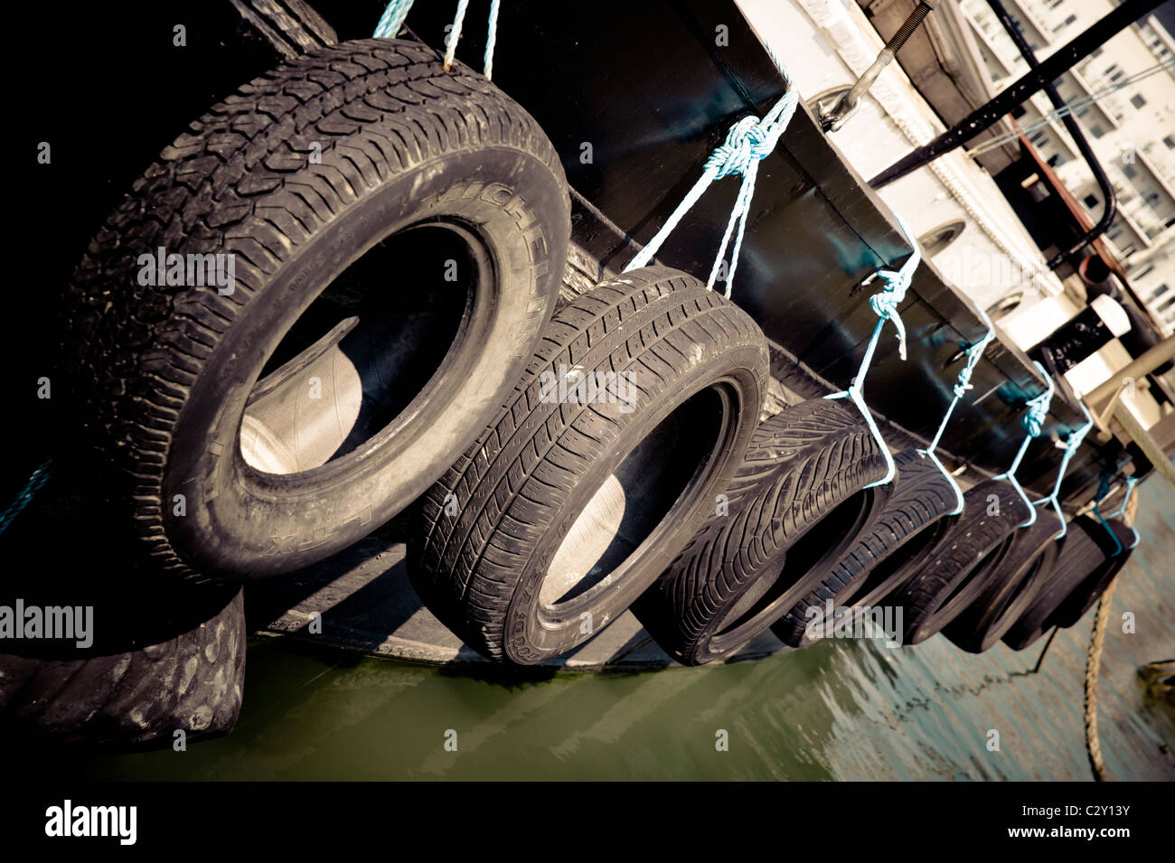 Tyres along the side of Wendy Ann 2, a tug style boat tied up on the river Arun in Littlehampton, West Sussex - Stock Image