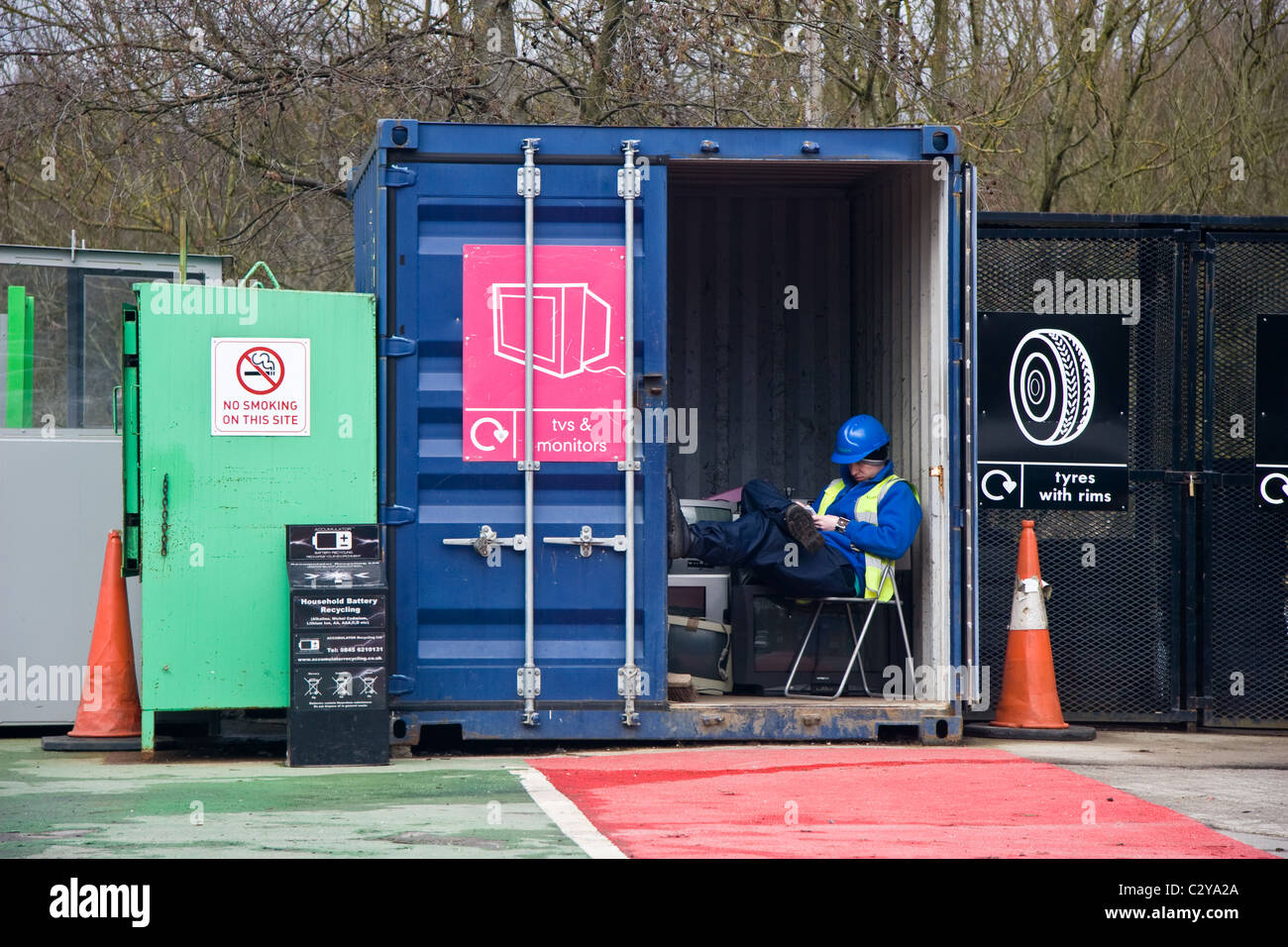 Attendant texting at household waste recycling centre, Prestwich, Bury, Greater Manchester, England, UK - Stock Image