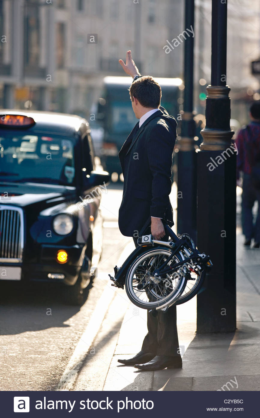 A businessman hailing a taxi, holding his folded bicycle - Stock Image