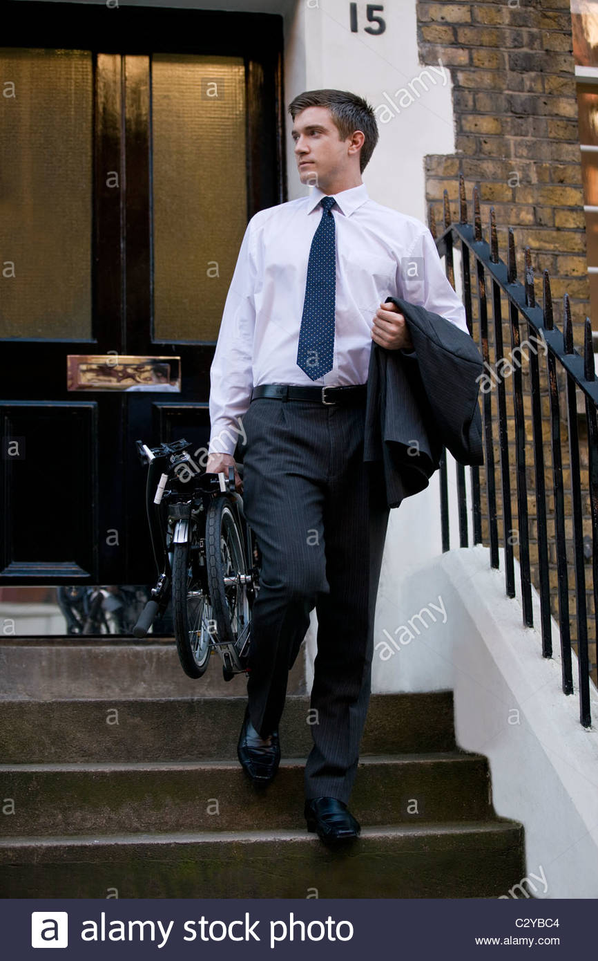A businessman leaving a building, holding a bicycle Stock Photo
