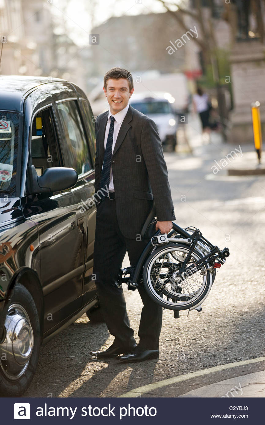 A businessman standing next to a taxi, holding his folded bicycle - Stock Image