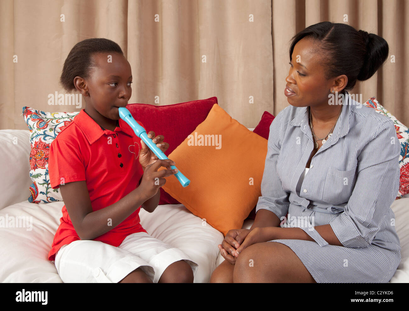 Mother listening to daughter playing recorder, Johannesburg, South Africa - Stock Image