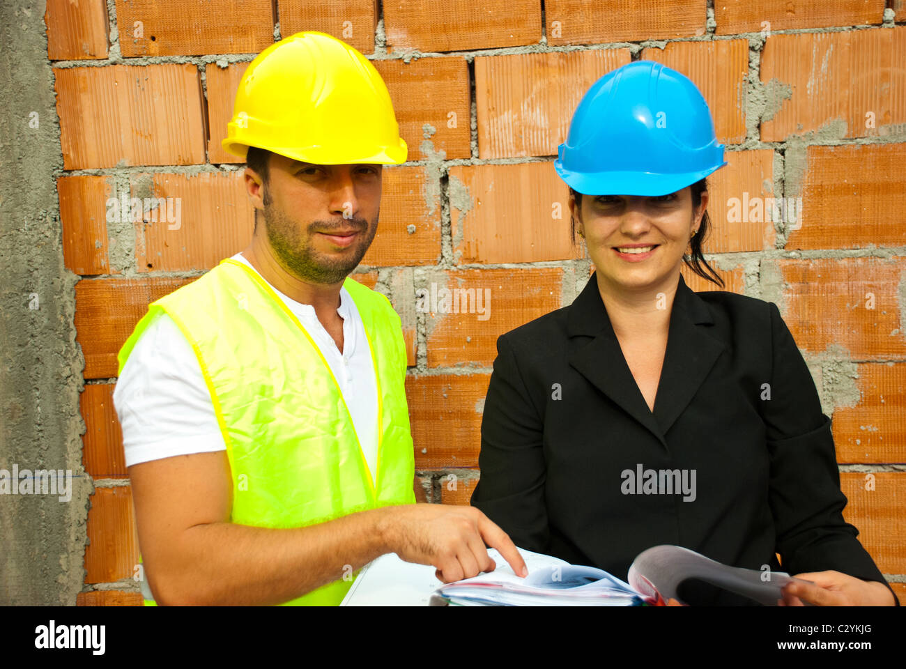 Two young smiling architects with plans working on site and holding plans,man pointing to paper Stock Photo