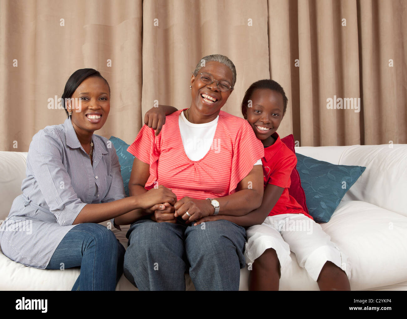 Three generations of women on the couch, Johannesburg, South Africa - Stock Image
