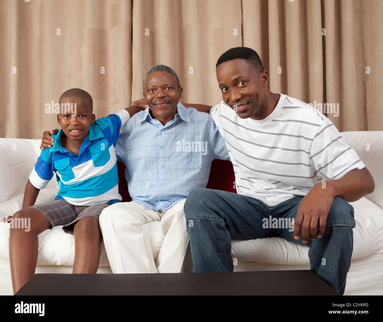 Three generations of men on the couch, Johannesburg, South Africa - Stock Image