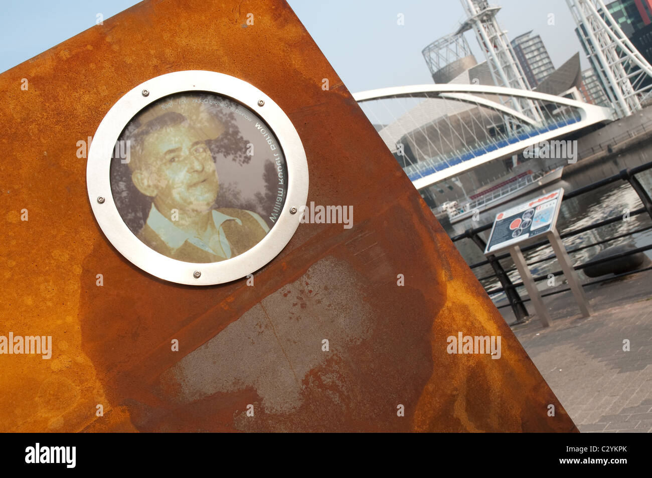 The 'Casuals' sculpture at Salford Quays.The portrait inserts are of workers at the former port. - Stock Image