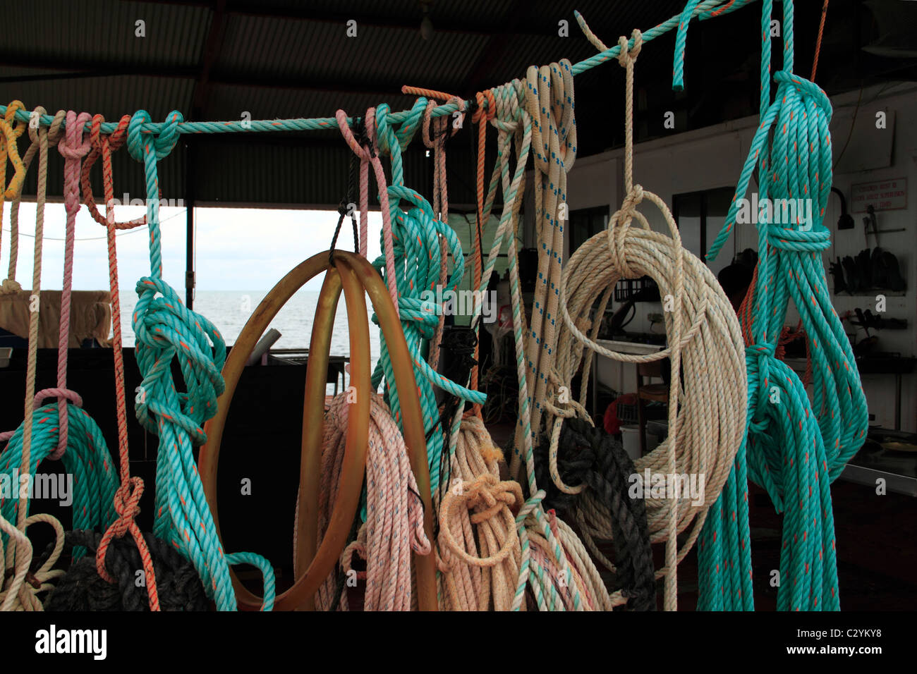 Various coloured nylon rope hanging from a line, Shark Bay, Northwest Australia - Stock Image