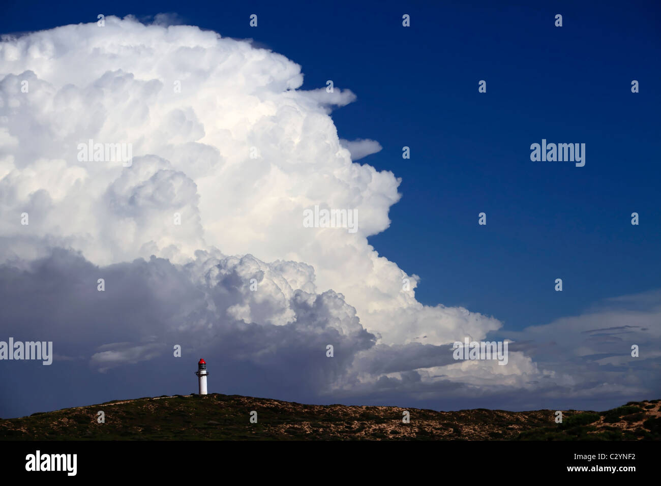 Point Quobba Lighthouse with big rain cloud in the distance, Northwest Australia - Stock Image