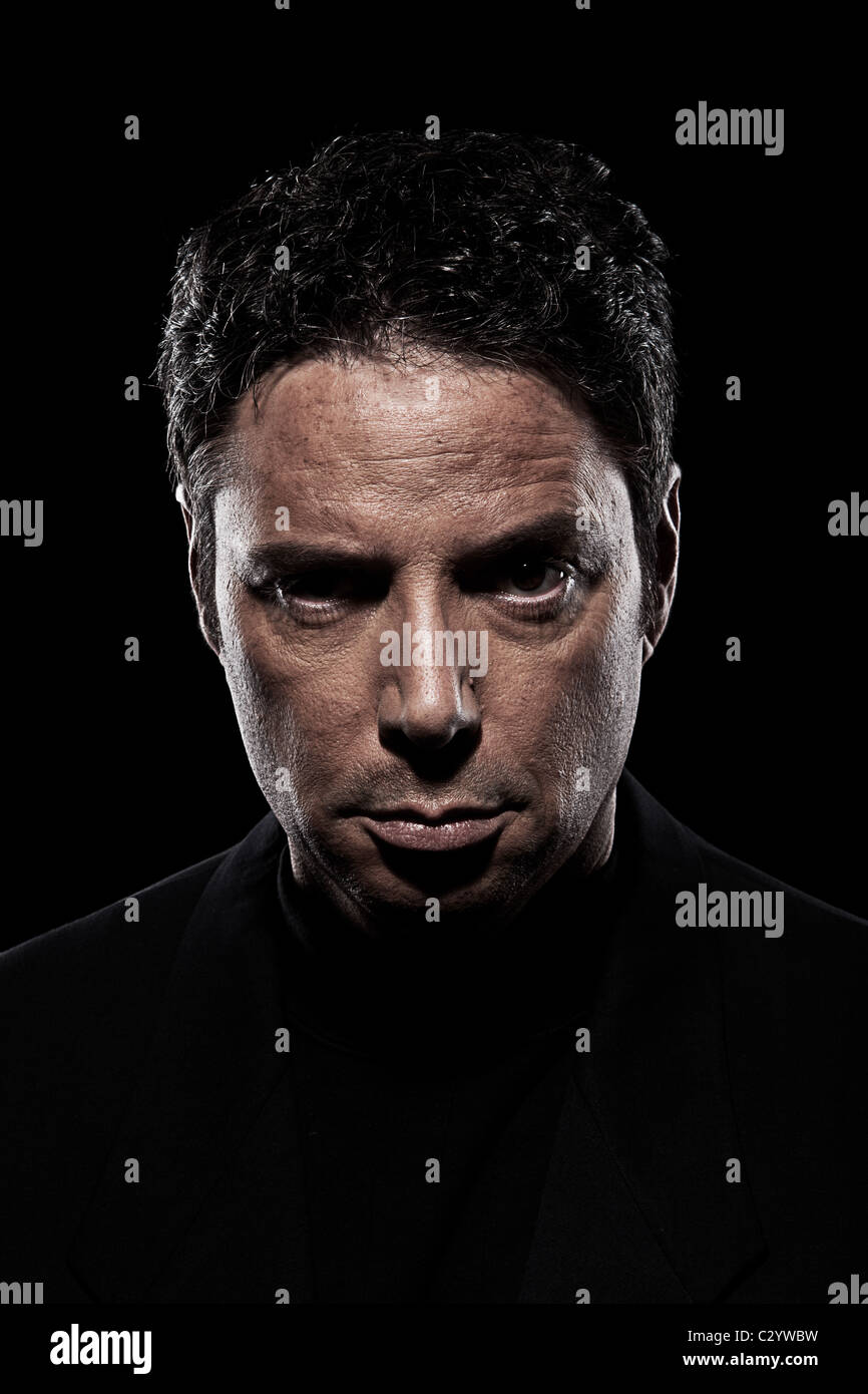 Angry, violent mobster wearing black in shadows - Stock Image