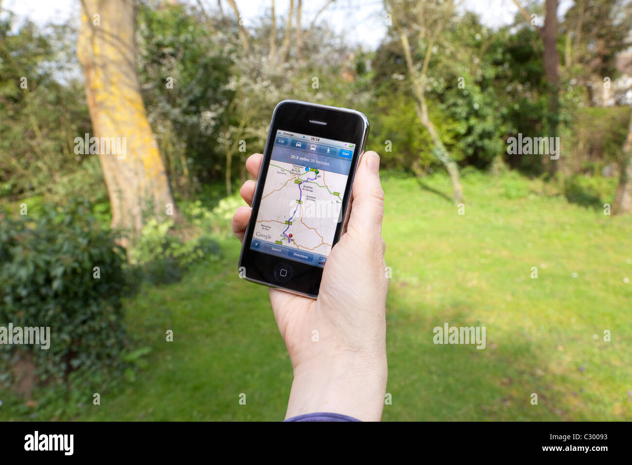person using iPhone for GPS / Satnav map on screen - Stock Image