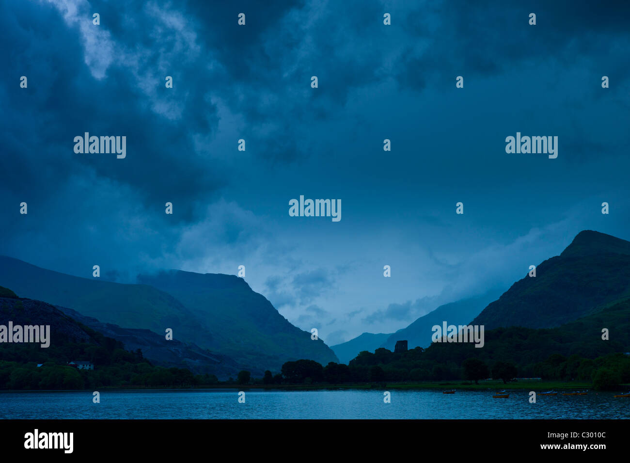 Llanberis Pass with Snowdonia on right, Dolbadarn Castle and Llyn Padarn lake, in Snowdonia National Park, Wales - Stock Image