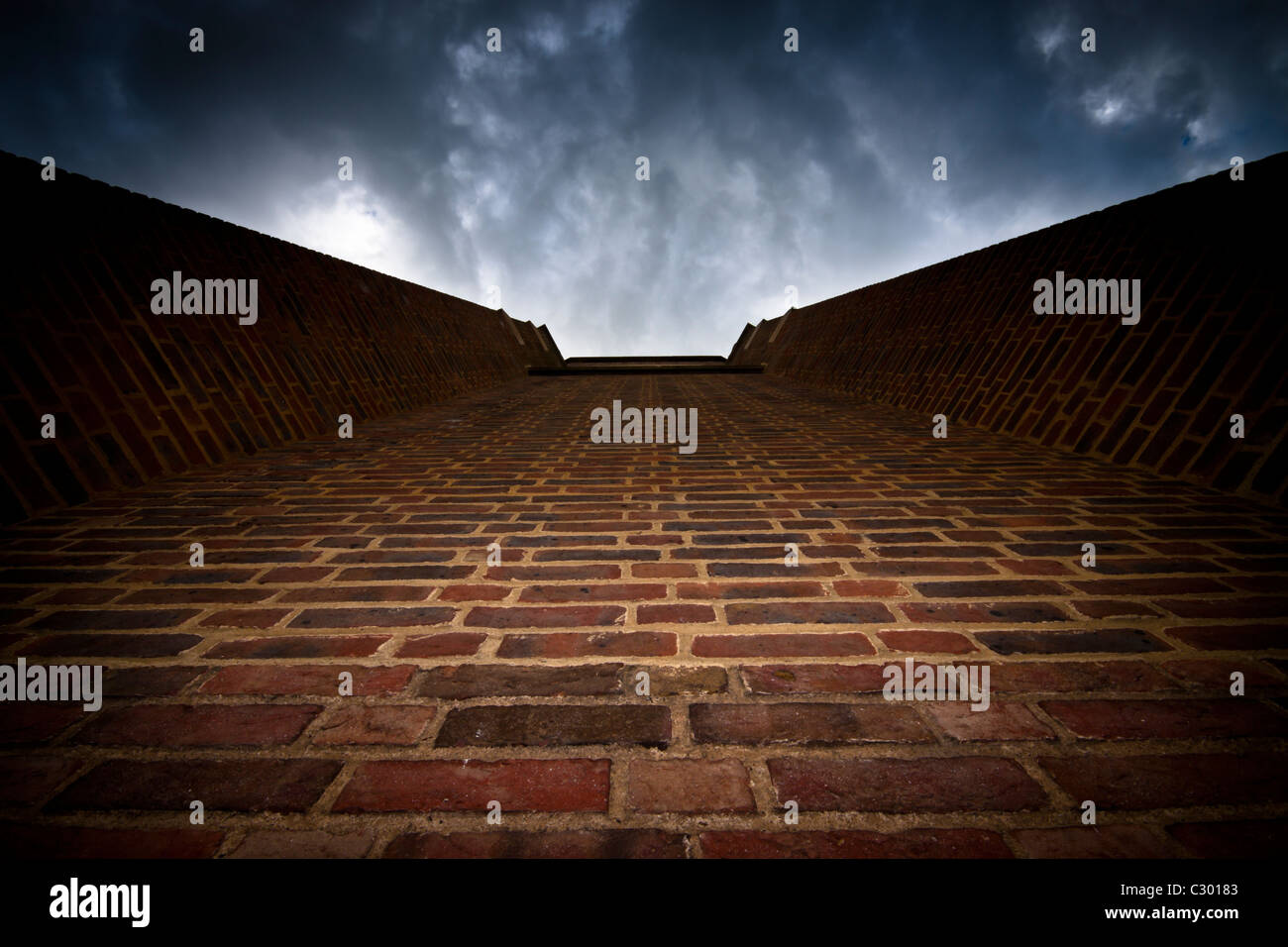 Abstract photo of brick wall and dramatic dark sky - Stock Image