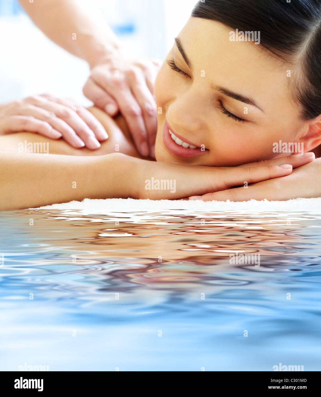 Smiling female during luxurious procedure of massage - Stock Image