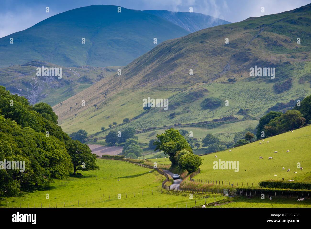 Car motoring along winding road through picturesque valley at Llanfihangel, Snowdonia, Gwynedd, Wales - Stock Image