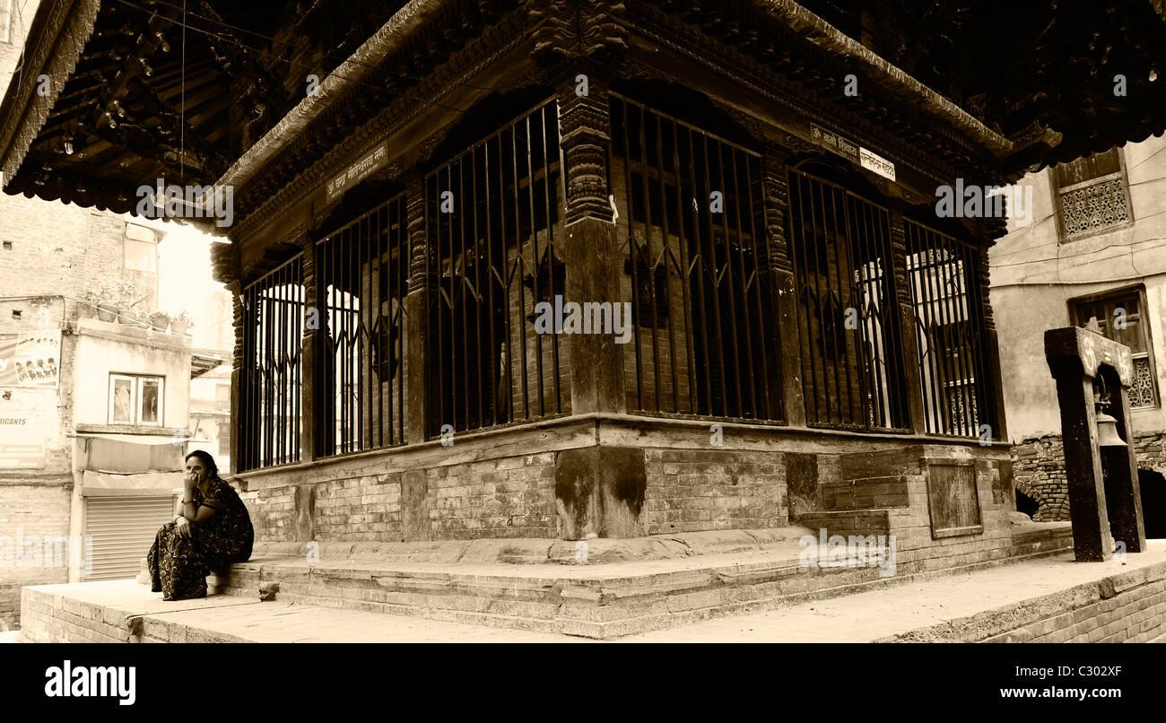 lady sitting by street shrine , life in kathmandu, nepal - Stock Image