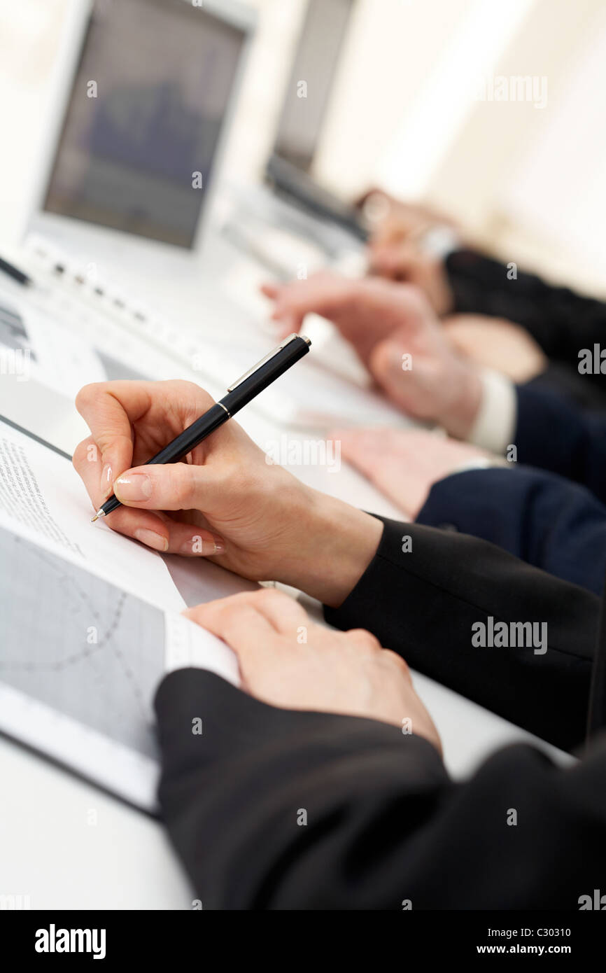 Image of human hand writing on paper at seminar or conference - Stock Image