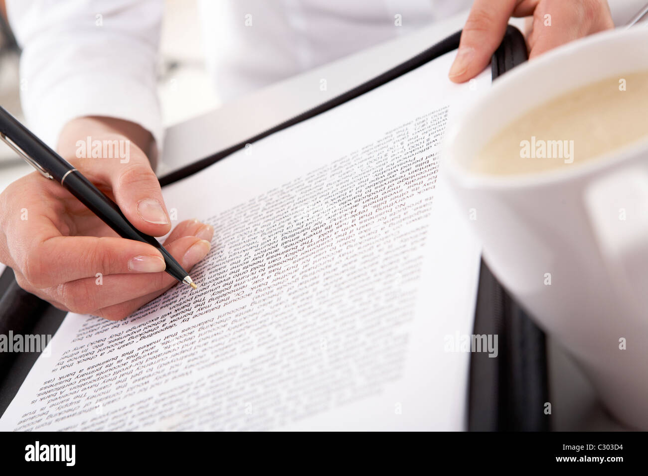 Close-up of businesswoman's hand holding pen over document with white cup near by Stock Photo
