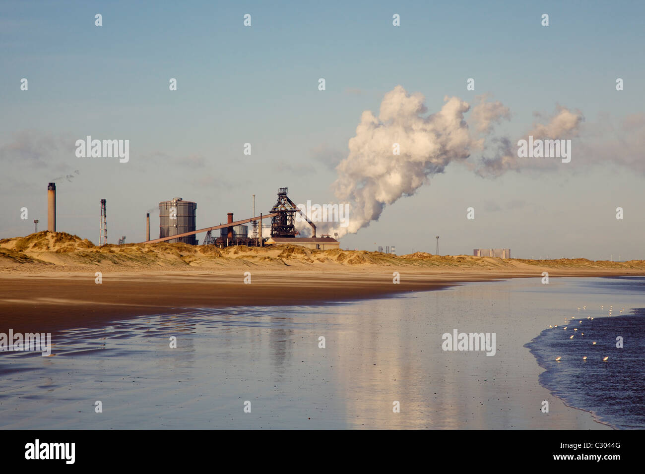 Steelworks at Redcar with steam and reflection in sea - Stock Image