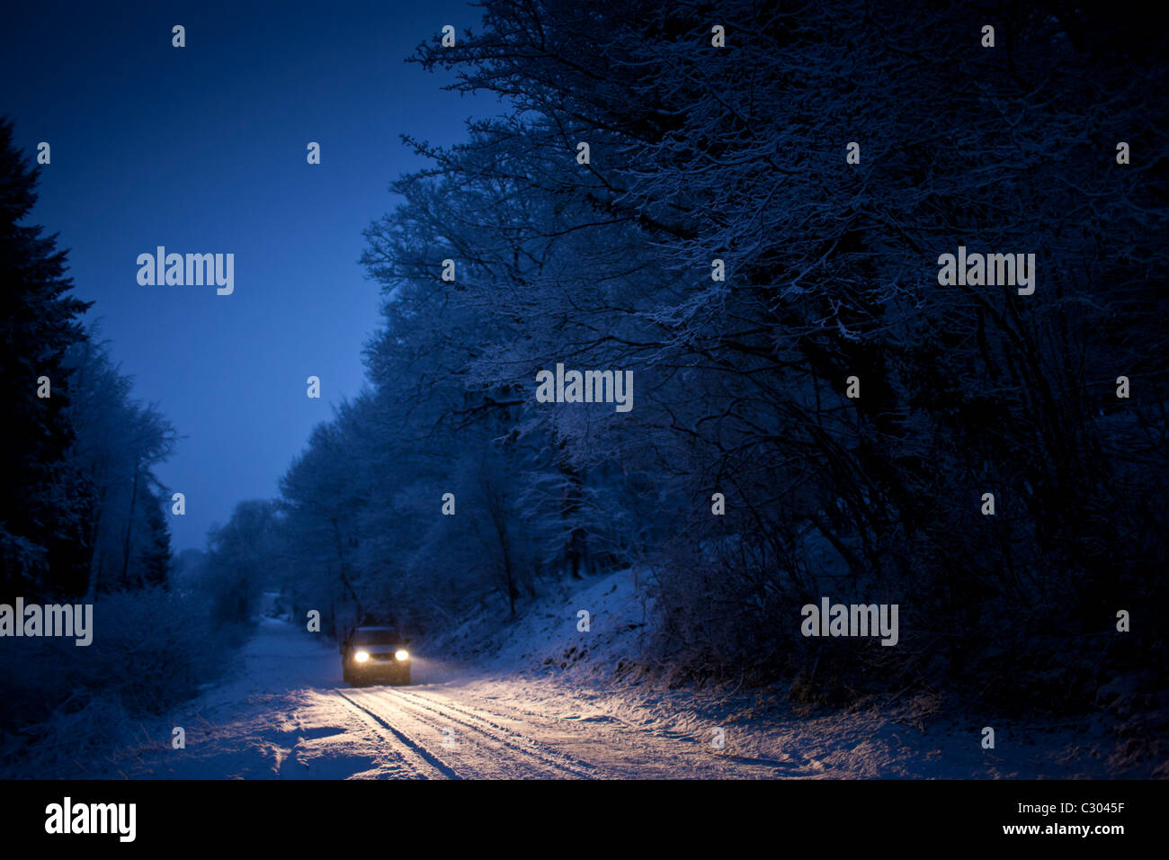 Four wheel drive car in traditional snow scene in The Cotswolds, Swinbrook, Oxfordshire, United Kingdom - Stock Image