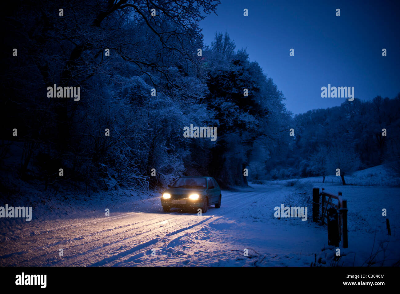 Small car drives slowly on icy road in The Cotswolds, Swinbrook, Oxfordshire, United Kingdom - Stock Image