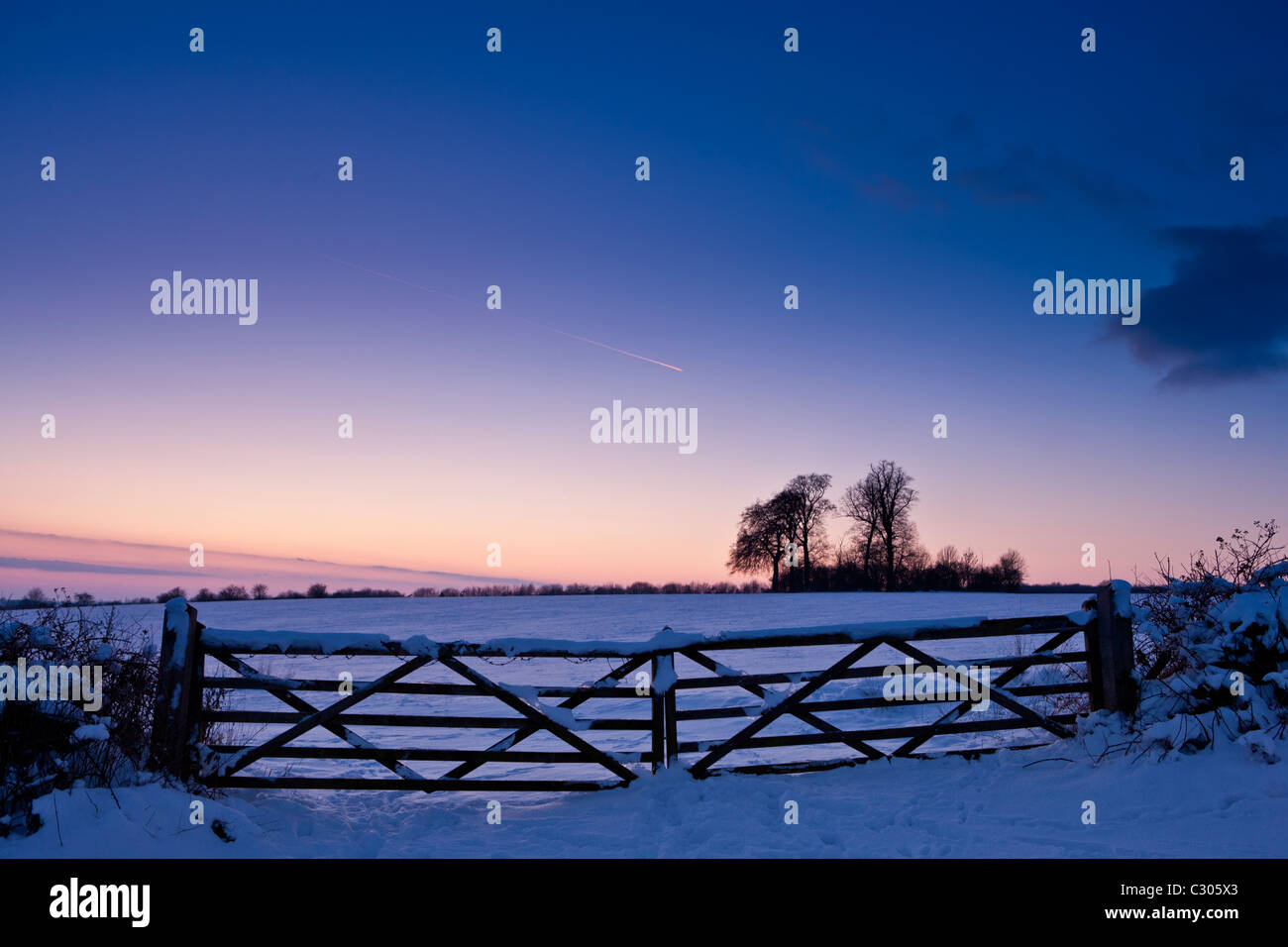 Farm gate in traditional snow scene in The Cotswolds, Swinbrook, Oxfordshire, United Kingdom - Stock Image