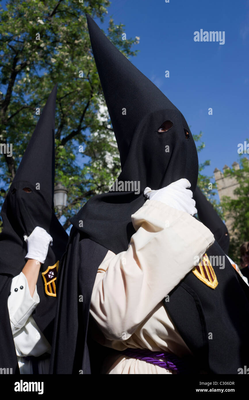 Hooded penitents (Nazarenos) gather for Seville's annual Semana Santa Easter passion processions. - Stock Image