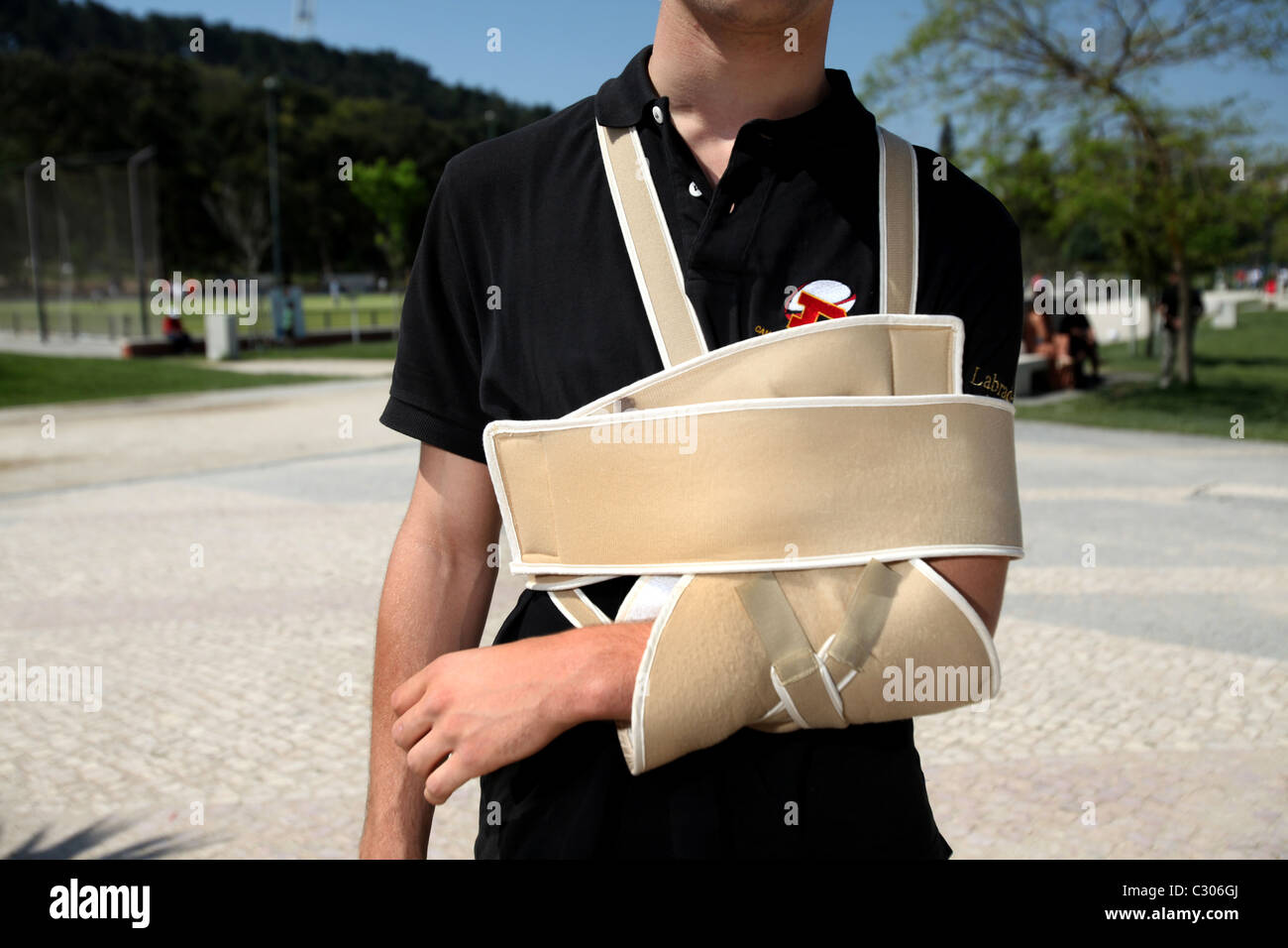 Young man with is arm in a sling. - Stock Image