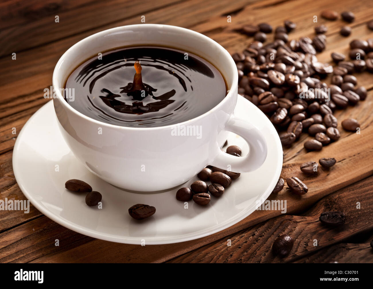 Drop falling into a cup of coffee. On a wooden background - Stock Image