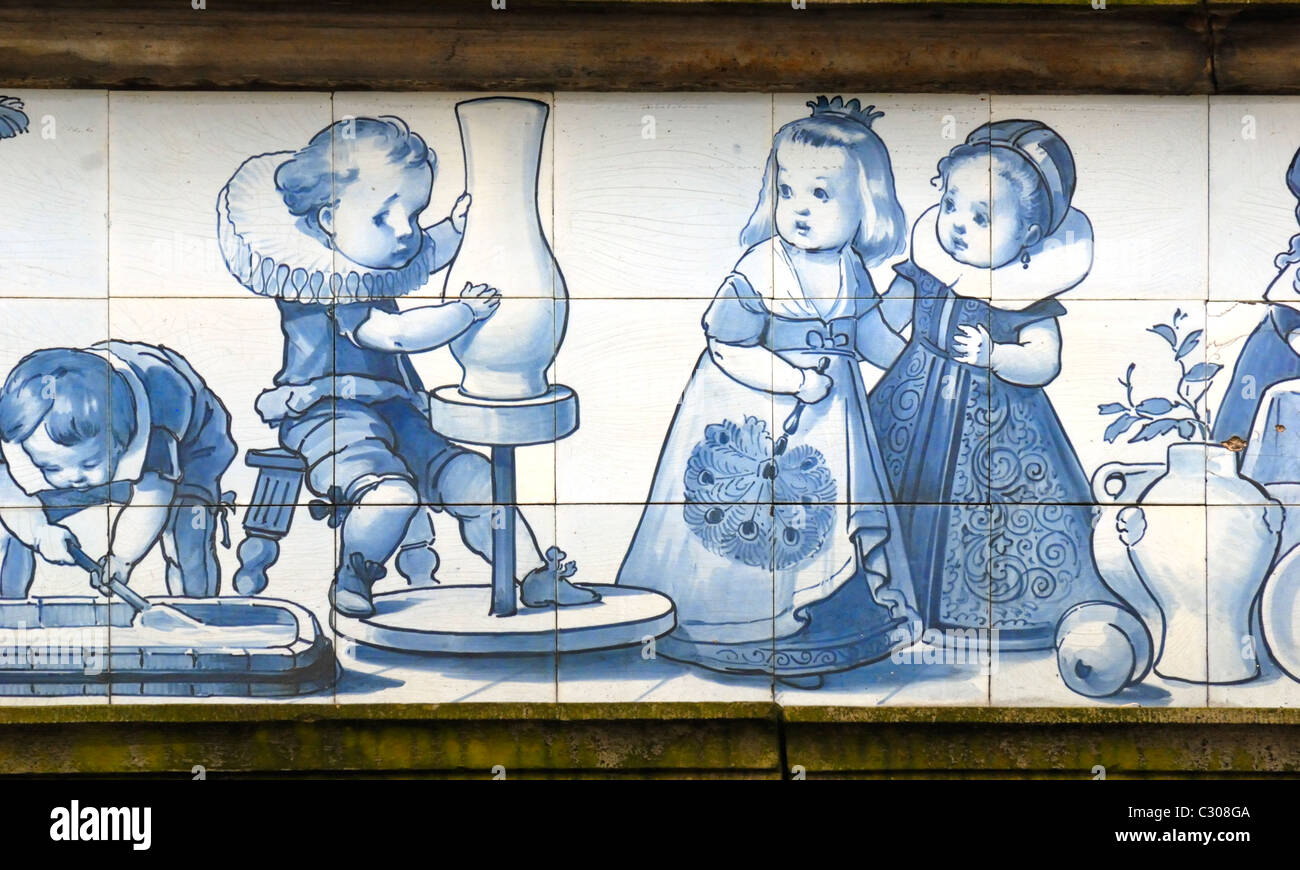 Delft, Netherlands. Blue and white Delft ceramic tiles above shopfront in Markt (main square) Young boy using a - Stock Image